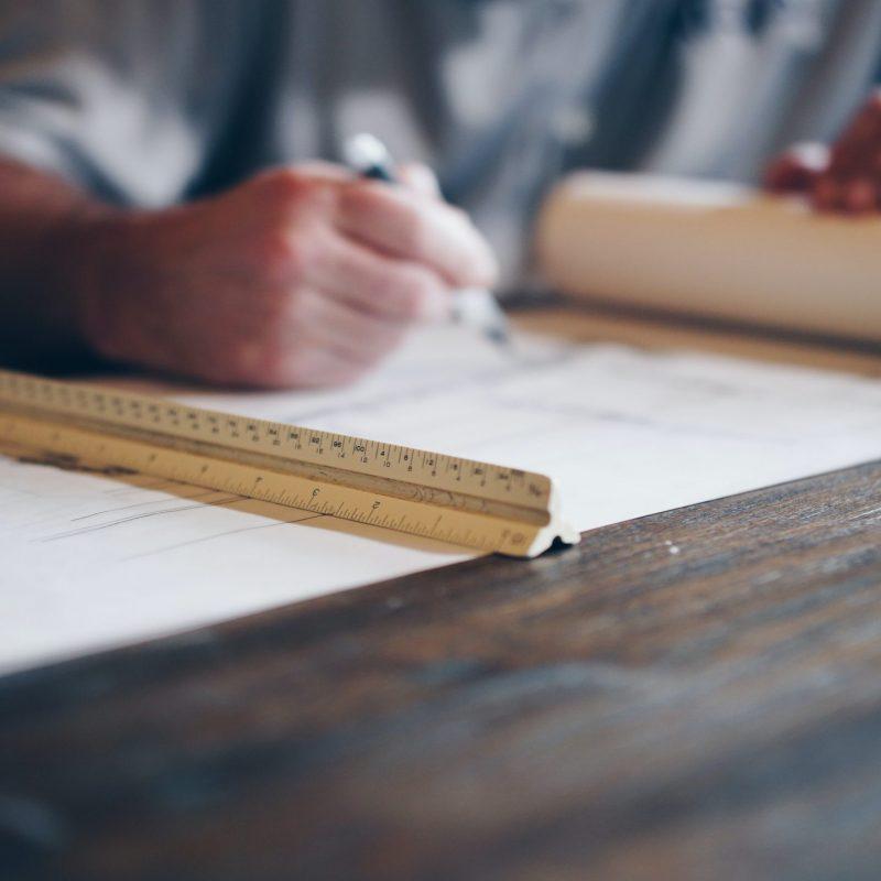 designer homes - architect designing building with ruler